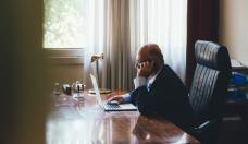 Senior businessman working with a laptop on his office