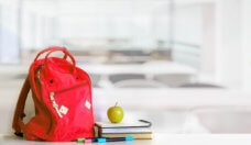 Red backpack and books school supplies in classroom.