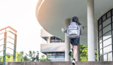 Back to school education concept with kid (elementary student girl) carrying backpacks going, running to class on school first day and walking up building stair happily