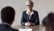Smiling middle-aged female job applicant making first impression at interview