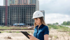 Female construction engineer. Architect with a tablet computer at a construction site. Young Woman looking, building site place on background. Construction concept