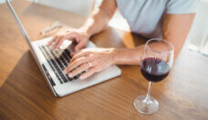 Focused senior man using laptop and drinking wine